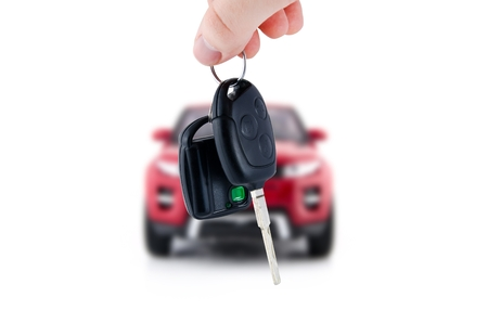 Hand holding keys to new red car. Buy or selling business composition Standard-Bild