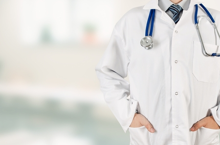 physician: Doctor with hands in pocket on blurred background. Copyspace medical, healthcare in hospital conception