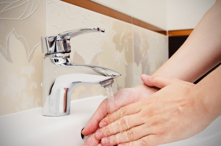 purely: Man washing hands in bathtoom. Utilities water bill cost rise wash hand composition