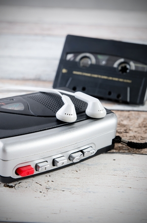 tape player: Old casette tape player and recorder with earphones on wooden background Stock Photo