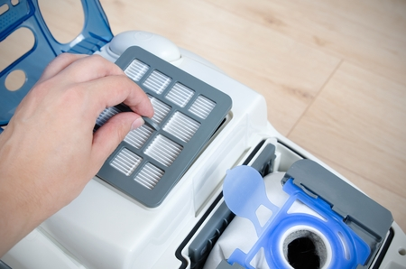 vacuum cleaner: Hand replacing the air filter in a modern vacuum cleaner Stock Photo