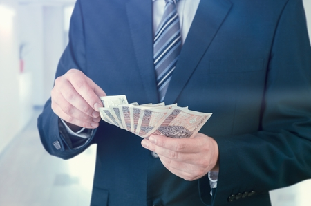 polish: Range of Polish banknotes in hand. businessman giving money loan polish zloty pln hand concept