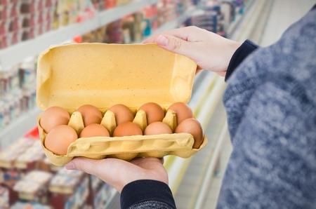 egg box: Man holding egg box in supermarket. egg box buy carton man hold checking consumer concept Stock Photo