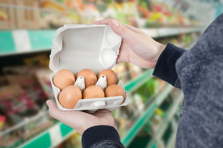 checking ingredients: Man holding egg box in supermarket. egg box buy carton man hold checking consumer concept Stock Photo