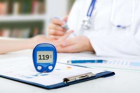 Arts controleert bloedsuikerspiegel. arts patiënt diabetes lancet glucometer bloed glucose kantoor concept