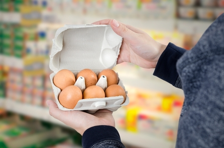 Man holding egg box in supermarket. egg box buy carton man hold checking consumer concept Stock Photo
