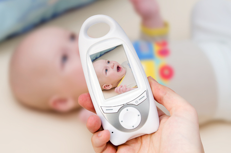 Hand holding video baby monitor for security of the baby Фото со стока
