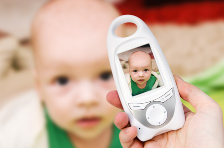 security monitor: Hand holding video baby monitor for security of the baby Stock Photo