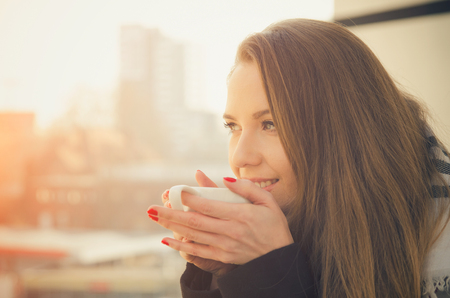 Woman drinking coffee or tea with cup on the balcony. coffee woman happy sun morning tea life beautiful concept