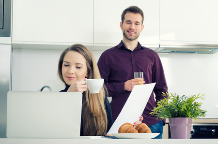 modern businesswoman: Young businesswoman working at home drinking coffee. home work woman laptop kitchen modern businesswoman couple concept
