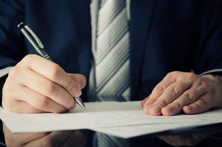 Businessman signs a contract. man contract signing hand writing pen letter paper concept Imagens