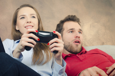 couple on couch: Pair spends free time playing video games. video game couple leisure play console watching gamepad concept