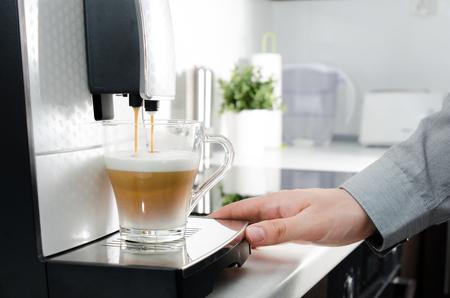 cappuccino cup: Home professional coffee machine with cappuccino cup. coffee machine latte macchiato cappuccino milk foam prepare concept