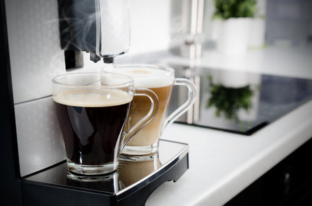 macchiato: Two cups of coffee, home professional coffee machine. coffee machine latte macchiato cappuccino espresso milk foam concept