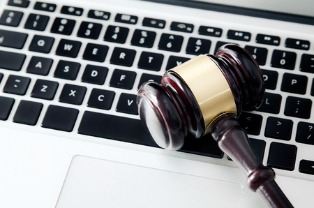 Martillo de madera en el teclado del ordenador portátil. Subasta, en línea, ley, tecnología, concepto de justicia