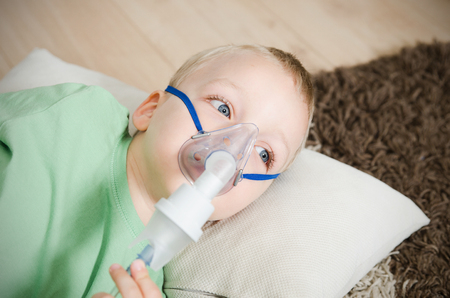 Boy making inhalation with nebulizer at home. child asthma inhaler inhalation nebulizer steam sick cough concept Stock Photo