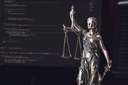 casualty: Justice statue with code on screen in background. Internet crime concept Stock Photo