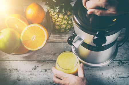 Man preparing fresh orange juice. Fruits in background on wooden desk Banque d'images