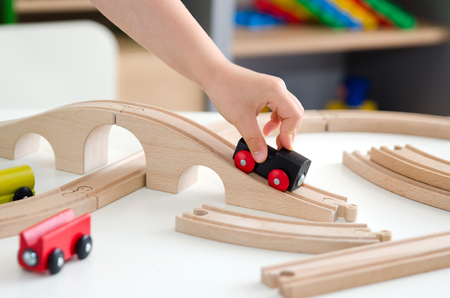 juguetes de madera: Child plays with a wooden toy train. toy wooden train toys education white background wood concept