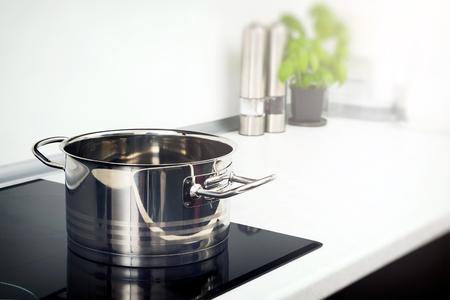 Olla en la cocina en la placa de inducción. Moderno cocina olla cocina inducción eléctrico estufa vitrocerámica Foto de archivo
