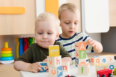 Kids boys playing with toy blocks at home or kindergarten. children kindergarten playing preschool daycare school child colorful concept Stock Photo