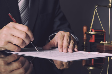 Attorney in suit working in office. law lawyer pen business man notary scale concept Banque d'images