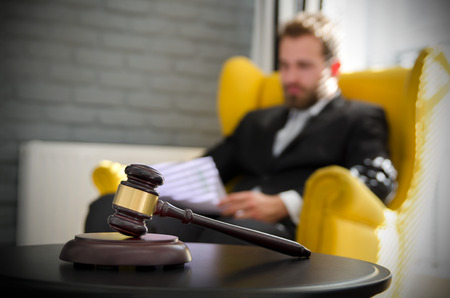 criminal: Wooden gavel, working lawyer in background. attorney business judgment justice suite analyzing authority background concept