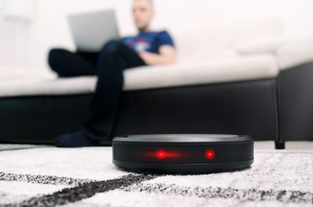 Robotic vacuum cleaner working on carpet. Abstract science fiction red eyes sensor concept Stock Photo