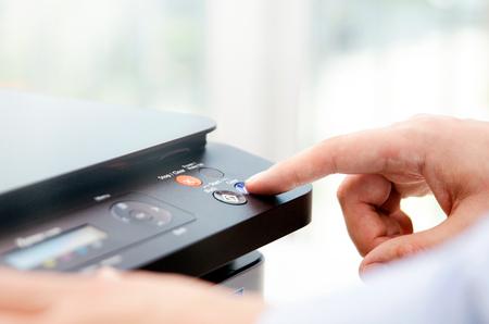 프린터 패널에 손으로 눌러 단추. 프린터 스캐너 레이저 오피스 복사기 공급 시작 개념 스톡 콘텐츠