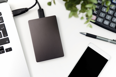 External backup disk hard drive connected to laptop. hard drive backup disk external computer data usb concept