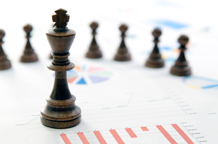 Chess business team leader. Financial strategy management with documents on desk concept.