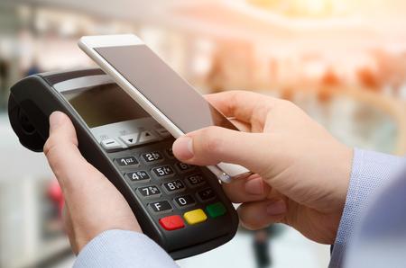 남자 신용 카드 지불 기계를 사용 하여입니다. 비접촉식 스마트 폰 응용 프로그램으로 모바일 지불