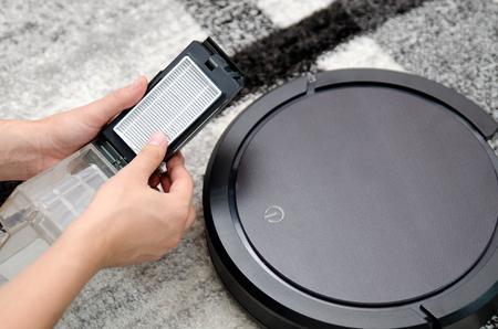 Robotic vacuum cleaner. Hepa filter cleaning. Maintenance concept.