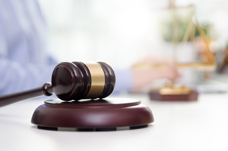 Wooden gavel, working lawyer in background. lawyer law justice judge gavel courtroom legal table concept Stock Photo