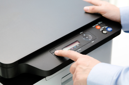 Hand press button on panel of printer. printer scanner laser office copy machine supplies start concept