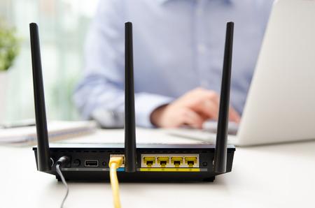 Enrutador inalámbrico y hombre usando una computadora portátil en la oficina. enrutador inalámbrico de banda ancha en casa computadora portátil teléfono wifi concepto