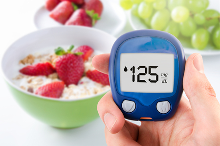 Hand holding meter. Diabetes doing glucose level test. Fruits in background Stock Photo