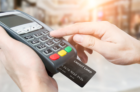 Hand with credit card swipe through terminal for sale in supermarket Stockfoto