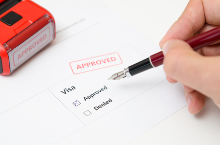 Visa and approved stamp on a document form. Immigration and travel concept Imagens