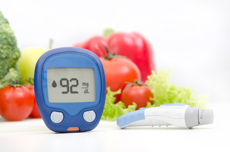 Glucometer and lancelet on vegetables background