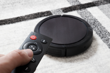 Robotic vacuum cleaner working on carpet. Hand holding remote control