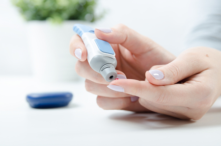 Diabetes doing blood glucose measurement. Woman using lancet and glucometer.