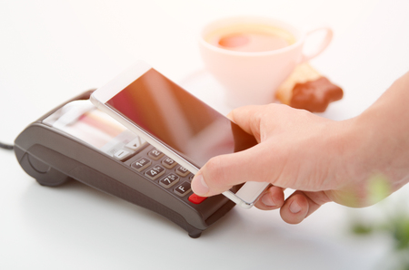 Mobile payment in cafe with smart phone nfc near field communication wireless technology Stockfoto