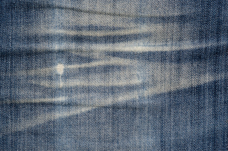 Texture of blue denim fabric. denim jeans material texture creased dirty background pattern concept