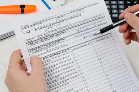 Man holding polish tax form VAT-7. Tax form law document poland business concept