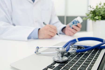 Doctor working in hospital. Stethoscope on laptop keyboard. Medical doctor healthcare consultation in polyclinic or hospital concept