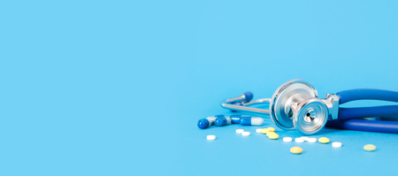 Stethoscope and pills on blue background copy space for web, internet banner