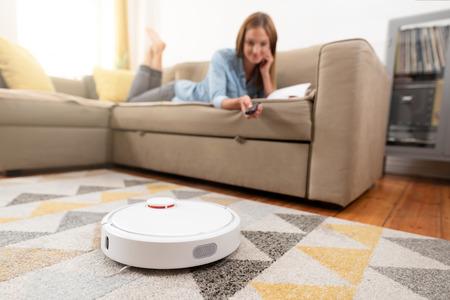 Aspiradora robótica limpiando la habitación mientras la mujer se relaja en el sofá. Mujer controlando el vacío con control remoto.