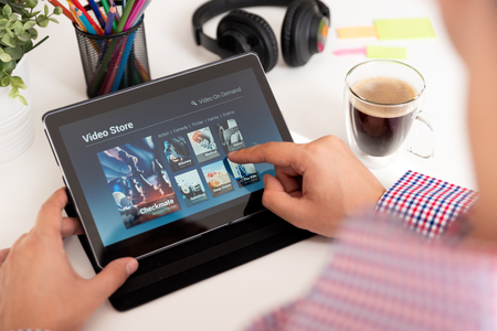 Man using digital tablet for watching movie on VOD service. Video On Demand television internet stream multimedia concept 版權商用圖片