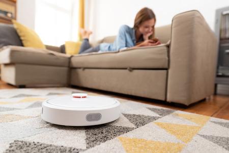 Aspiradora robótica limpiando la habitación mientras la mujer se relaja en el sofá. Mujer controlando el vacío con control remoto. Foto de archivo
